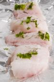 Raw monk fish with herbs on tin foil poster