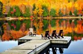 Wooden dock with chairs on calm fall lake poster