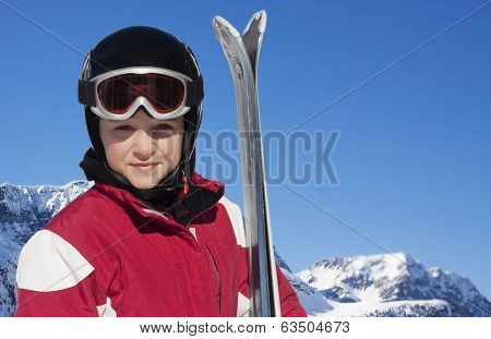 Child With Skis, Helmet And Goggles In The Skiing Slope