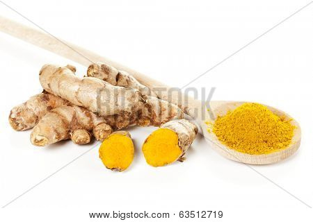 Turmeric rhizomes and ground turmeric on wooden spoon, isolated on white background