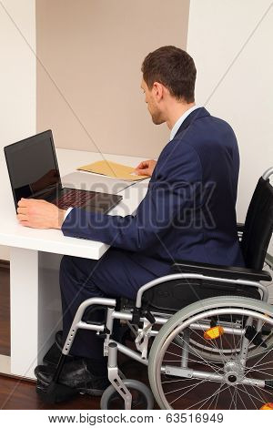 Businessman On A Wheelchair On His Desk