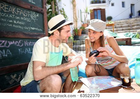 Couple of tourists relaxing and checking on pictures