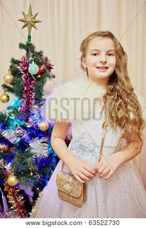 Portrait of girl dressed in festal dress standing near decorated christmas firtree in room