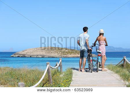 Couple standing by gorgeous beach with bicycles