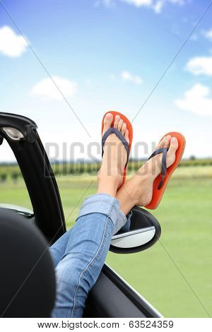 Closeup of feet with flip flops showing by car window