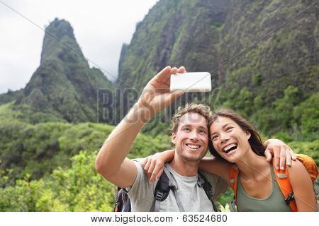 Couple taking selfie photo with smart phone hiking on Hawaii. Woman and man hiker taking photo with smart phone camera. Healthy lifestyle from Iao Valley State Park, Wailuku, Maui, Hawaii, USA. poster