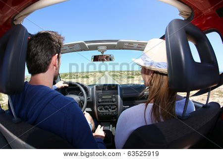 Back view of couple driving convertible car