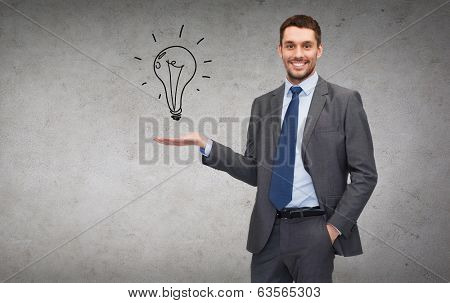 business, office, advertising and people concept - friendly young buisnessman showing light bulb on the palm of his hand