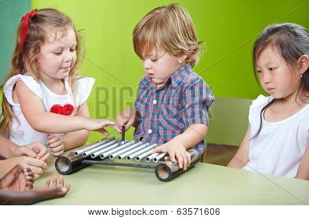 Boy playing xylophone in kindergarten at musical education
