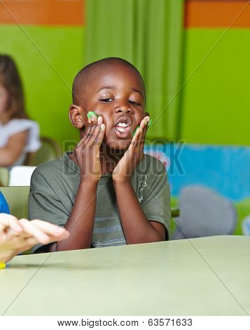Silly african child making nonsense with dough in a kindergarten