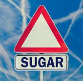 Sugar danger warning composed of white triangular traffic warning sign with the word - Sugar - below against a blue sky criss-crossed with contrails conceptual of the dangers of sugar in the diet. poster