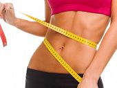 sport, fitness and diet concept - close up of trained belly with measuring tape poster