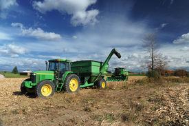 Green Tractor In The Farm Field
