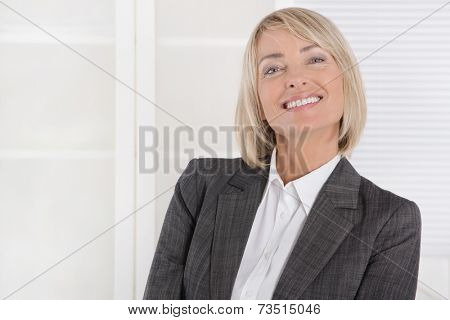 Attractive smiling middle aged businesswoman in portrait wearing business outfit.