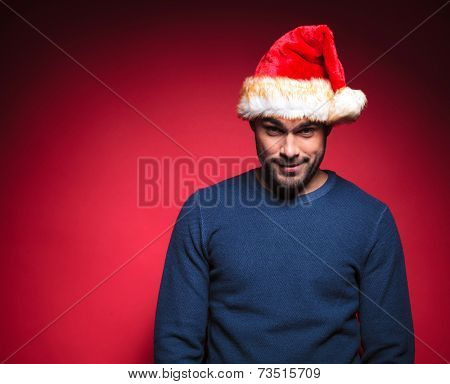 Hadsome man in blue sweater wearing a red santa hat looking at the camera, smiling. On red background.