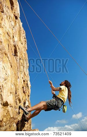 A man in a harness holding on to a rope while climbing up a steep mountain -Rockclimbing