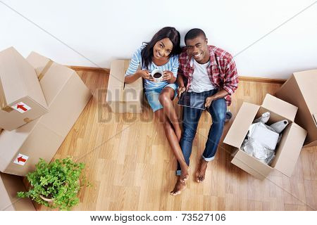 overhead view of young black african couple with moving boxes in new apartment using modern tablet computer technology