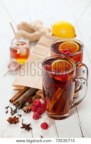 Cup Of Hot Winter Raspberry Tea With Cinnamon Sticks, Lemon And Star Anise