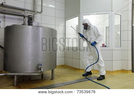 technician in white protective uniform,mask,gloves with high pressure washer at large industrial process tank cleaning floor in plant