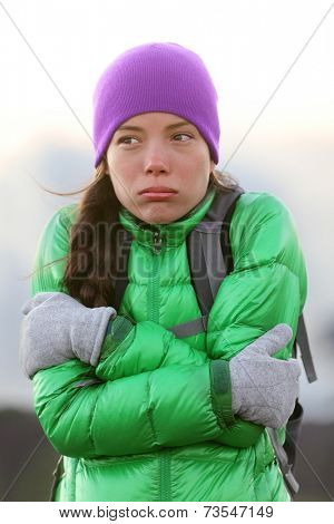Freezing woman feeling cold outdoors trying to keep warm shaking and shivering wearing hat and gloves outside hiking on hike.