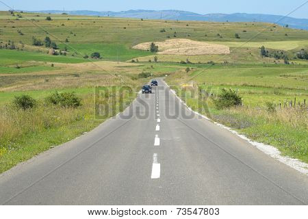 straight road crosses rural area of Pester plateau, Serbia