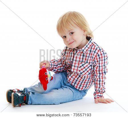 Little boy sitting on the floor teddybear .