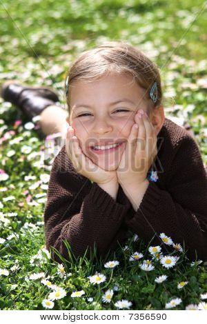 Girl lying in field of daisies