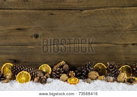 Natural christmas decoration with oranges, nuts and fir cone on wooden background. poster
