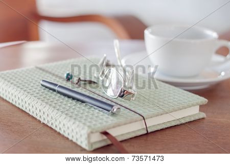 Notebook With Pen, Eyeglasses And White Coffee Cup On Wooden Table