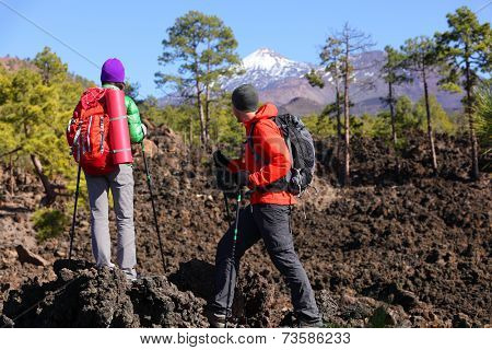 People hiking - healthy active lifestyle hikers. Hiker couple hiking in beautiful mountain nature landscape. Woman and man hikers walking during hike on volcano Teide, Tenerife, Canary Islands, Spain.