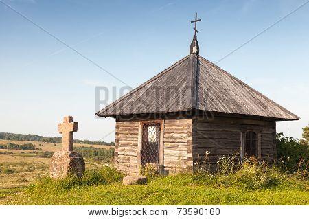 Ancient wooden Orthodox chapel and a stone cross on Savkina gorka Pskov Region Russia poster