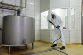technician in white protective uniform,mask,gloves with high pressure washer at large industrial process tank cleaning floor in plant poster