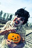 a scary zombie with a carved pumpkin at abandoned railroad tracks, with a filter effect poster