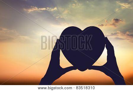 Hand holding a heart shape symbol