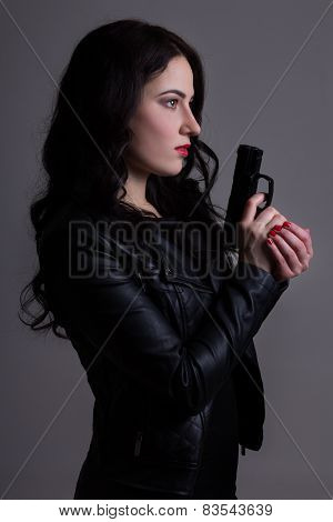 Portrait Of Sexy Woman In Black With Gun Over Grey