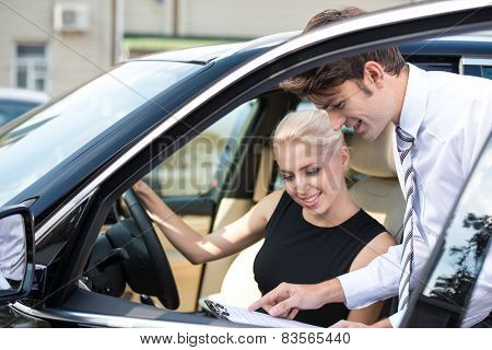 Car dealer and young woman signing a contract