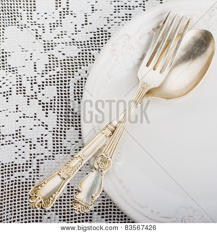 Closeup of vintage lacy white cloth handmade German silver fork and spoon