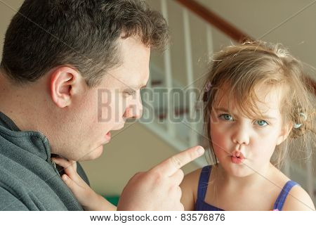 Little girl getting spoken to by her father