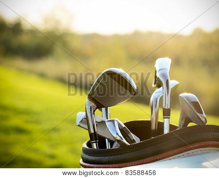 Golf clubs drivers over green field background. Summer sunset poster