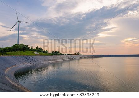 Wind Turbine Generating Electricity On Dam Catchment