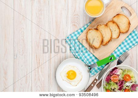 Healthy breakfast with fried egg, toasts and salad on white wooden table. Top view with copy space poster
