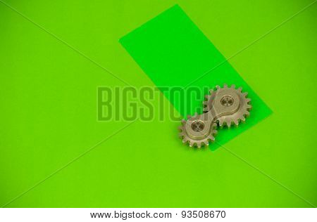 Double cogwheel connected industrial element shot on vivid green paper background
