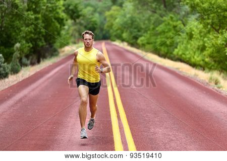 Running man runner sprinting for fitness and health. Young male athlete in sprint run wearing sports running shoes and shorts in workout for marathon. Full body length view of sprinter.