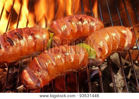 Two Skewers With Sausage On The Hot Bbq Flaming Grill