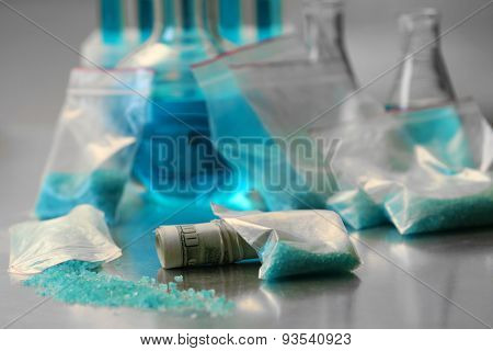 Drug laboratory: blue methamphetamine and money on table close up