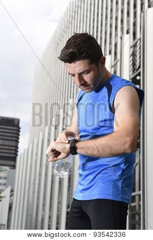 Young Sport Man Checking Time On Chrono Timer Runners Watch Holding Water Bottle After Training Sess