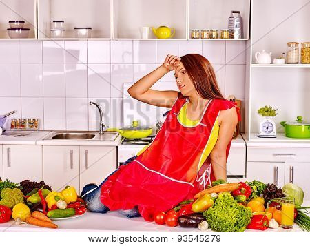 Unhappy tired woman inred apron preparing food at kitchen.