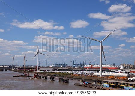 LONDON, ENGLAND - JUN 7 2015 : The Tilbury Docks wind turbines rest easy on a windless afternoon.