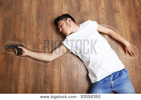 Crime scene simulation, young man lying with gun on floor poster