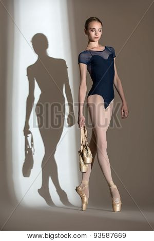 Full growth portrait of the graceful ballerina in a studio